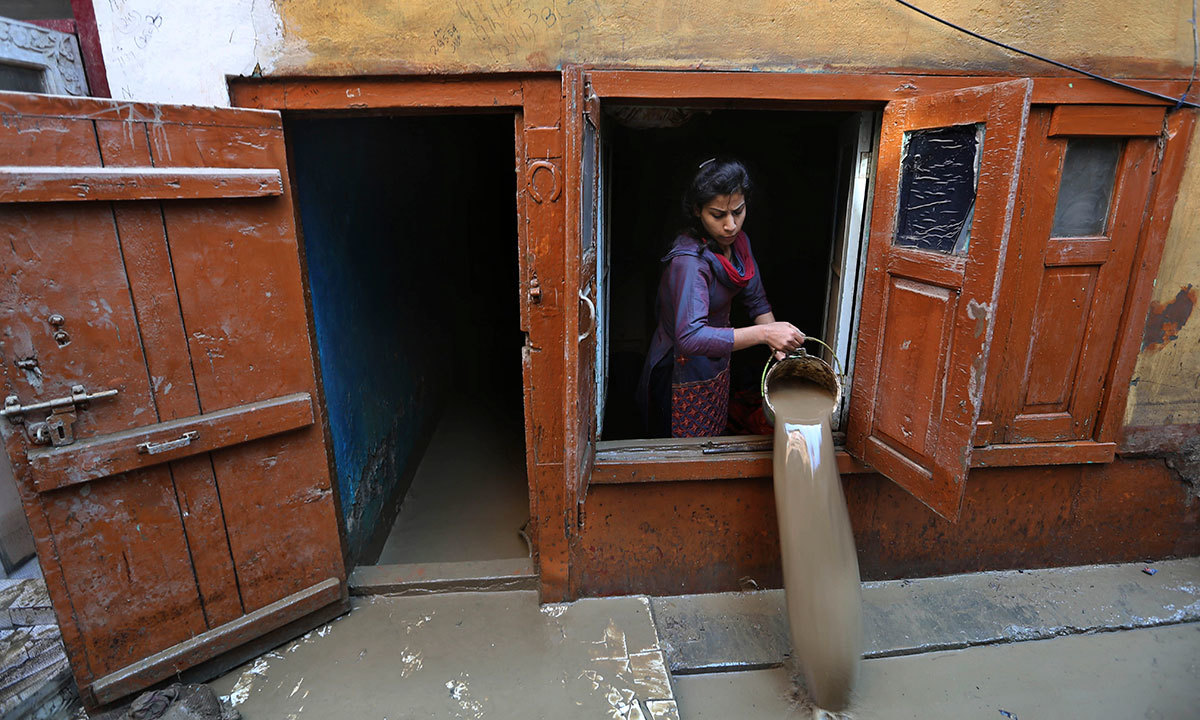 A Kashmiri woman drains muddy water from her flood damaged house in Srinagar, Indian-held Kashmir, Thursday, Sept.18, 2014. — Photo by AP