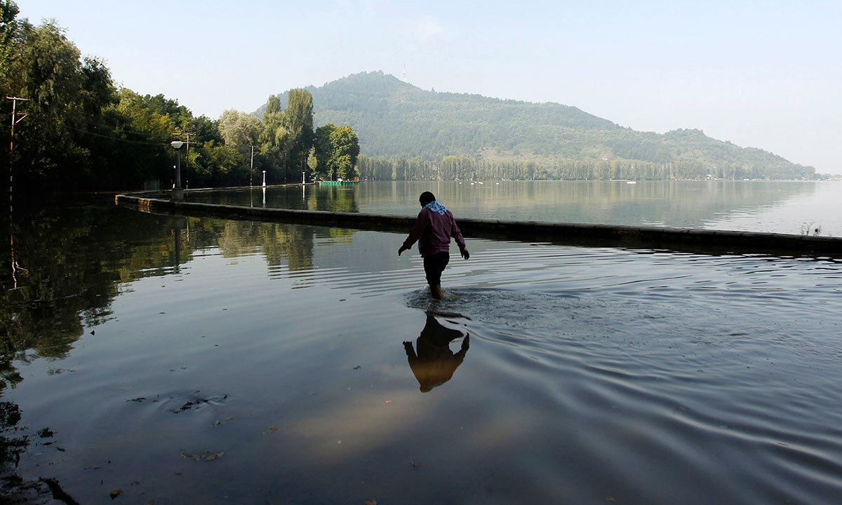 A man wades through a flooded road along the banks of Dal Lake in Srinagar September 18, 2014. — Photo by AFP