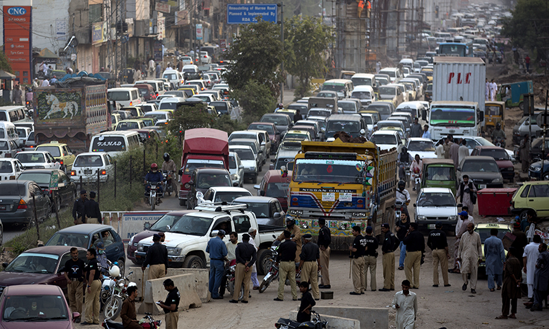 Police block traffic to refrain supporters of PTI from entering the capital to attend anti-government rally.— Photo by AP