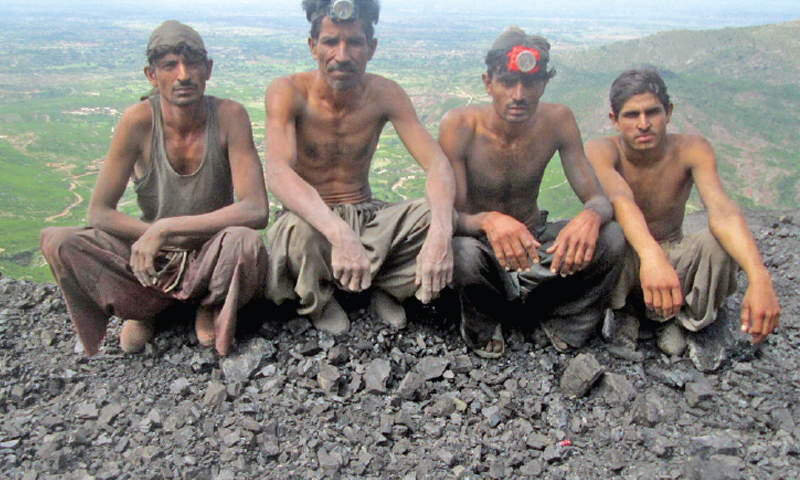 Miners pose as they sit on a heap of extracted coal.