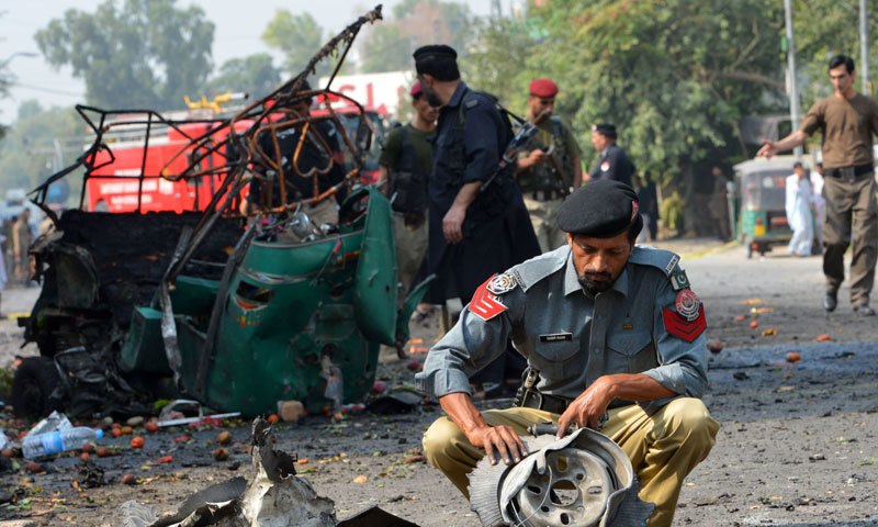 A police officer collects evidence from the site of a bomb attack on a Frontier Corps (FC) convoy in Peshawar September 23, 2014. At least three people were killed and several injured in the bomb attack targeting the FC convoy on Tuesday, according to local media. — Photo by Reuters