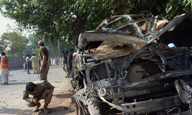 A military officer examines wreckage of a vehicle at the site of a suicide bomb attack in Peshawar on September 23, 2014. — Photo by AFP
