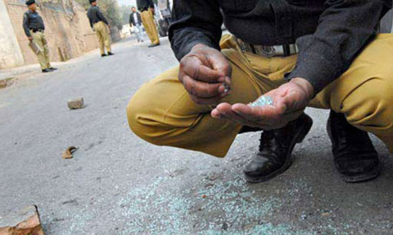This picture shows a policeman collecting evidence from a crime site. — File photo