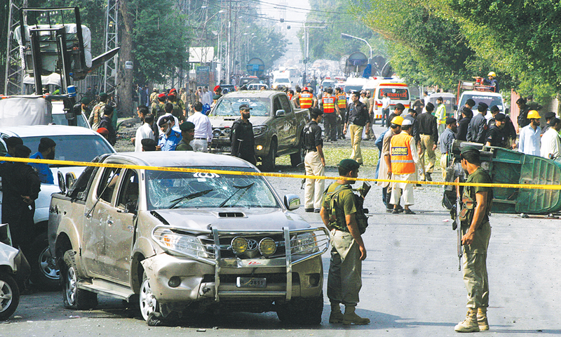 PESHAWAR: Security personnel and rescue workers gather at the site of the bomb blast here on Tuesday.—AP