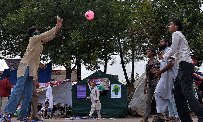 Supporters of Tahirul Qadri play handball as they camp in front of the Parliament building in Islamabad on September 24, 2014. – AFP Photo