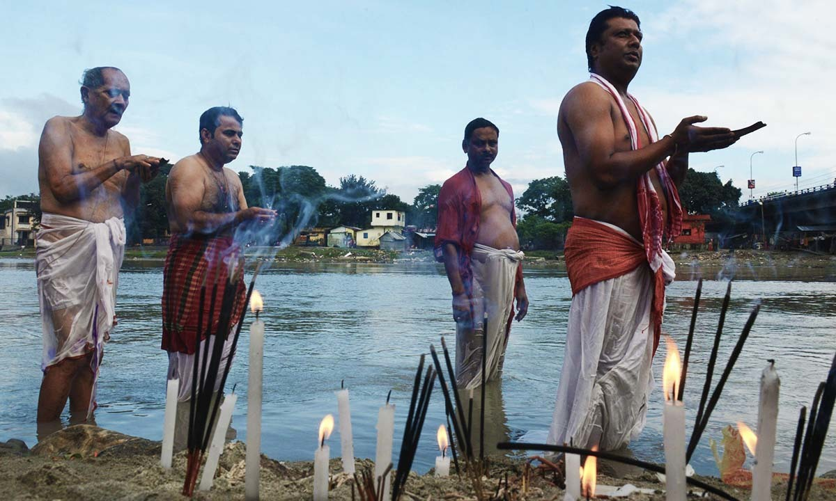 Devotees perform 'Tarpan', a ritual to pay obeisance to one's forefathers, on the last day of 'Pitrupaksh' - days for offering prayers to ancestors - on the banks of the river Mahananda in Siliguri on September 23, 2014. — Photo by AFP