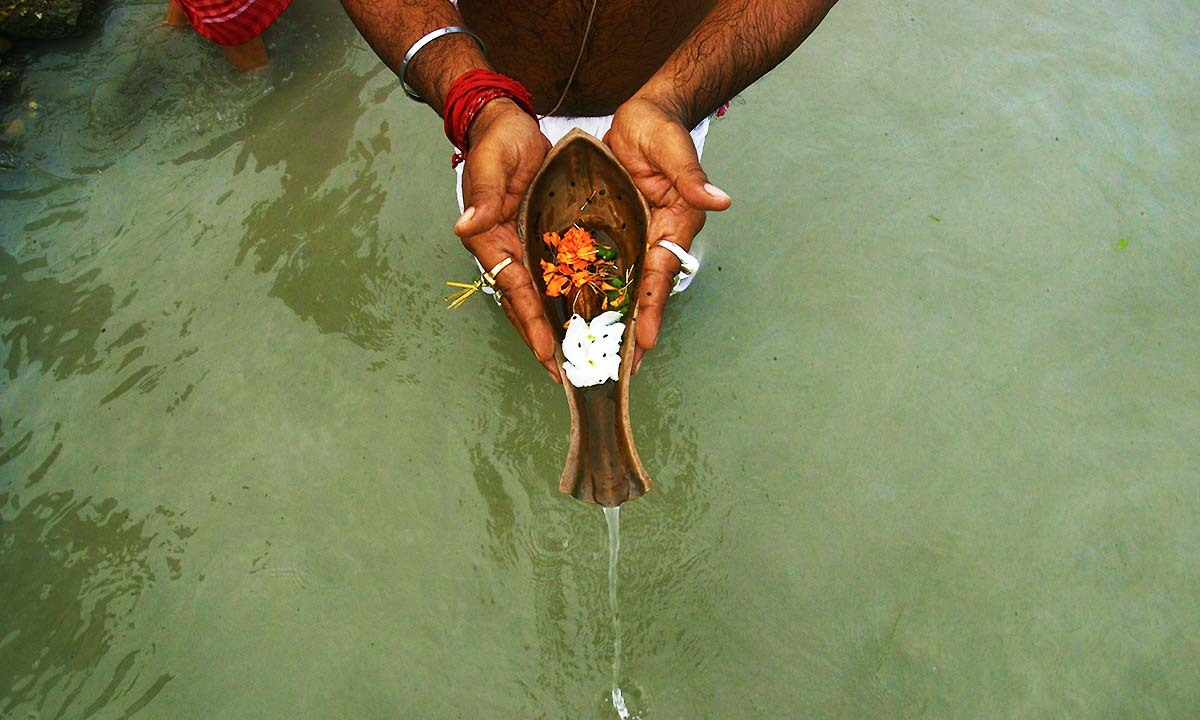 Devotee performs 'Tarpan', a ritual to pay obeisance to one's forefathers, on the last day of 'Pitrupaksh' - days for offering prayers to ancestors - on the banks of the river Mahananda in Siliguri on September 23, 2014.— Photo by AFP