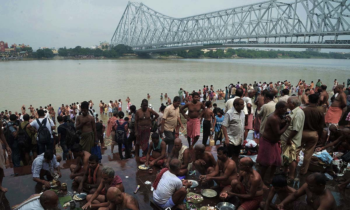 "Devotees perform 'Tarpan' rituals to pay obeisance to their forefathers on the last day of ""Pitrupaksh"", or days for offering prayers to ancestors, on the banks of the River Ganges in Kolkata on September 23, 2014.— Photo by AFP"