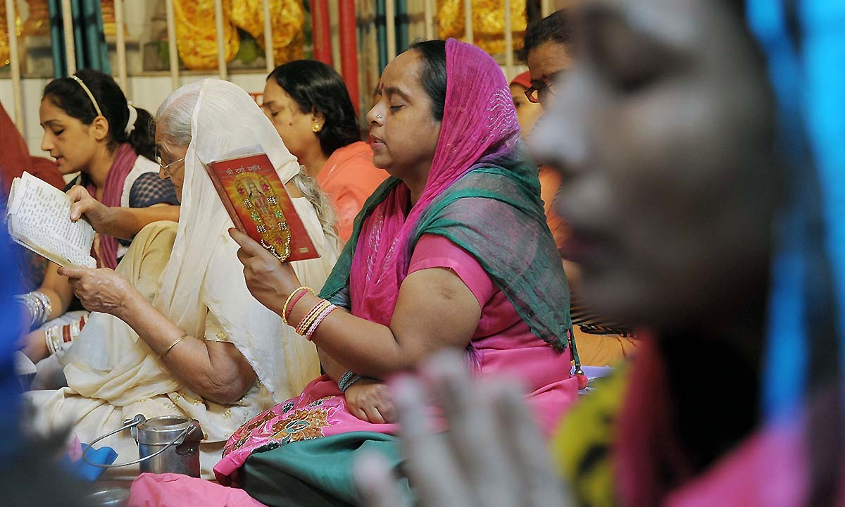 Indian Hindu devotees read the 'Durga Stuati' text during prayers for the Navratri Festival at the Mata Longa Wali Devi temple in Amritsar on September 25, 2014. Navratri is celebrated twice a year during the spring and autumn seasons and symbolises the triumph of good over evil.— Photo by AFP