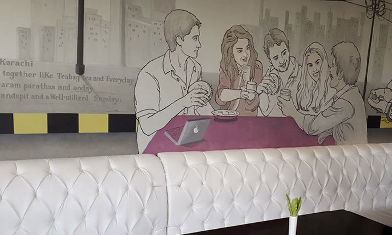 Mural shows friends eating burgers with an iMac on the table. – Photo by author