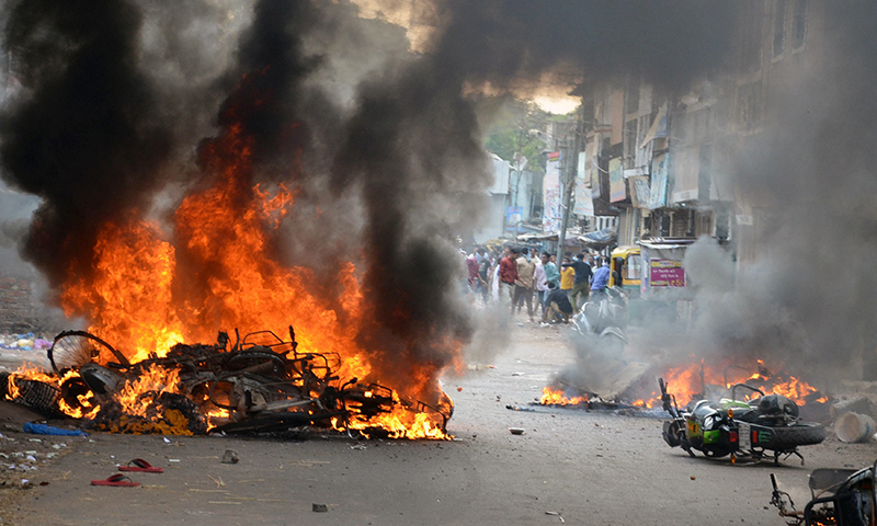Vehicles were set on fire by a mob during a clash in Vadodara. — Photo by Reuters