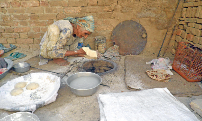 Siftian Bibi prepares Roti at a Tandoor in old Chaklala city. — Dawn
