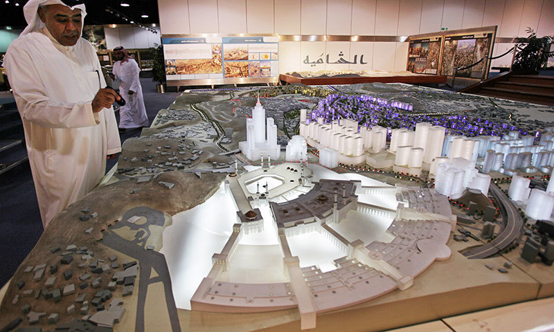 In this photo taken May 11, 2014, Essam Kalthoum, left, managing director of the Bawabat Makkah Company, which oversees several projects around the city, shows at his office in Jiddah, Saudi Arabia, a prototype of what the heart of Makkah will look like after construction around the Grand Mosque is complete. — Photo by AP