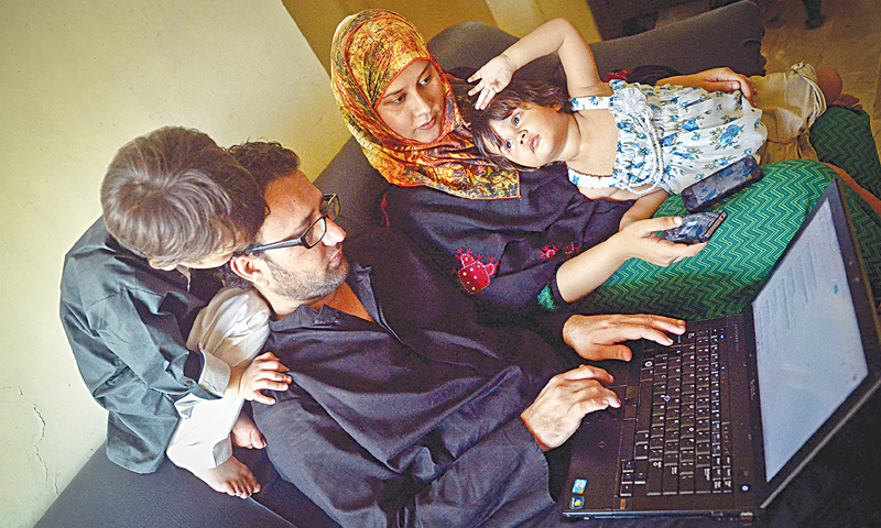 FAIZULLAH Khan, his wife Sania Faiz and their children crowd around a laptop as they search the internet for news about his detention and release, in their apartment in Gulistan-i-Jauhar on Wednesday.—Fahim Siddiqi / White Star