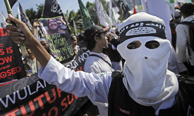 In this June 18, 2014 photo, a Muslim man wears a headband showing the Islamic State group's symbol during a protest calling for the closure of a local prostitution complex in Surabaya, Indonesia. — Photo by AP