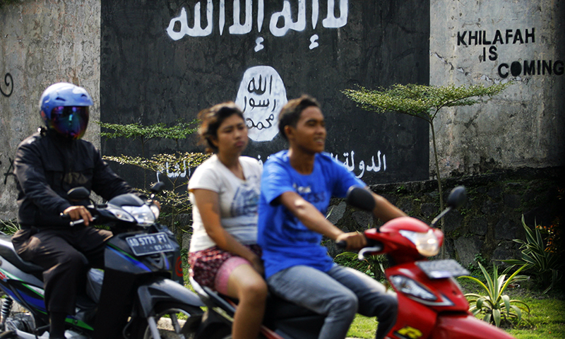 In this March 8, 2014 photo, motorists ride past a graffiti of the Islamic State group's flag in Solo, Central Java, Indonesia. — Photo by AP