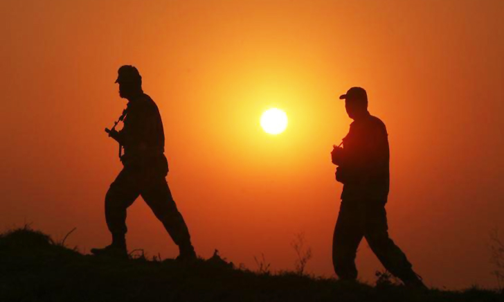 Border Security Force (BSF) soldiers patrol as they are silhouetted against the setting sun at the fenced border with Pakistan at Babiya village in Hira Nagar sector, about 80 km (50 miles) from Jammu December 6, 2013. - Reuters