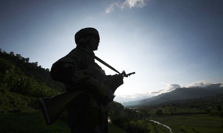 An Indian army soldier stands guard while patrolling near the Line of Control, a ceasefire line dividing Kashmir between India and Pakistan, in Poonch district August 7, 2013 in this file photo. - Reuters