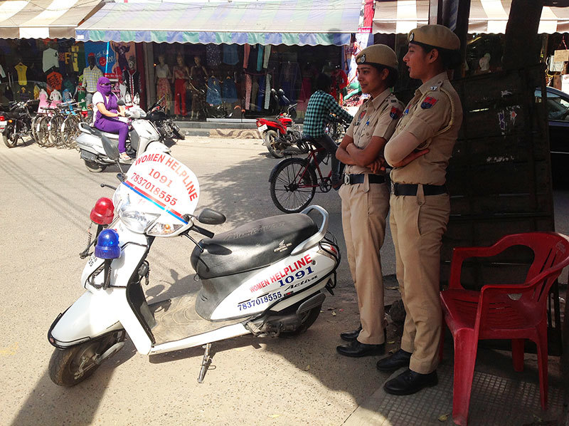 Two women police officers on duty in a Ludhiana bazaar with their Women Helpline scooty.