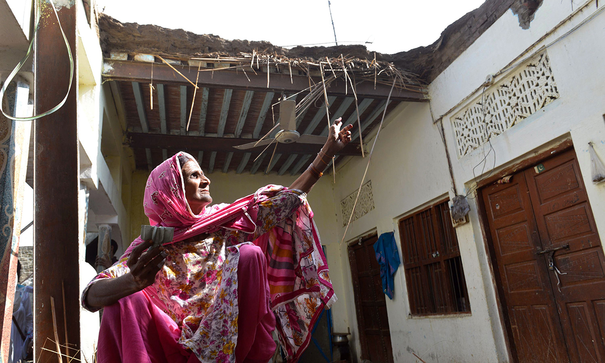 A Pakistani woman gestures as she sits beneath the damaged roof of her house, allegedly caused by shells fired by Indian troops, at the Dhamala border village near the city of Sialkot in Punjab on October 8, 2014. — Photo by AFP