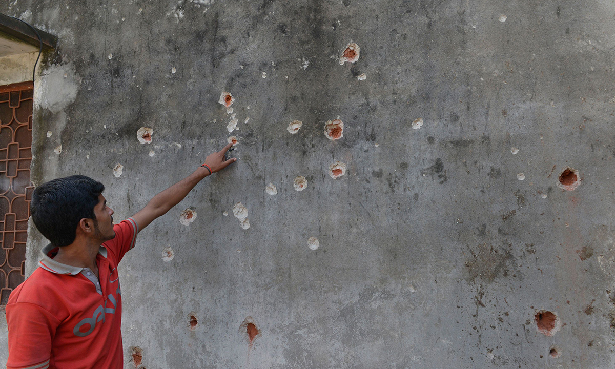A Pakistani resident points to bullet holes in the wall of his home, allegedly caused by shells fired by Indian troops, at the Dhamala border village near the city of Sialkot in Punjab on October 8, 2014. — Photo by AFP