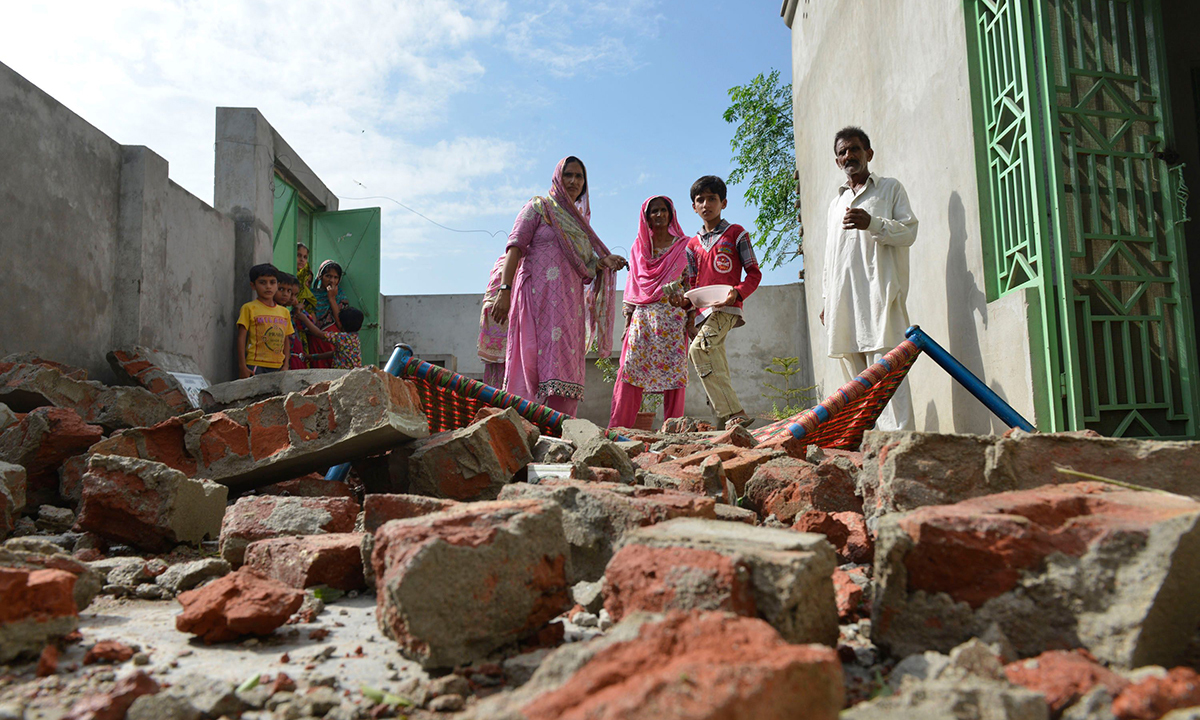 Pakistani residents gather at a damaged house, allegedly caused by shells fired by Indian troops, at the Dhamala border village near the city of Sialkot in Punjab on October 8, 2014. — Photo by AFP