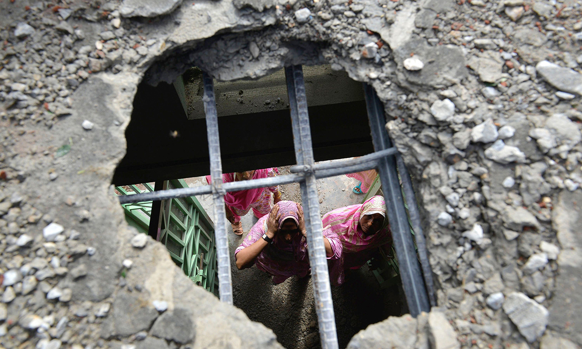 Pakistani villager women are seen through a hole in their house roof caused by a mortar shell allegedly fired across the border at the Dhamala border village near the city of Sialkot in Punjab on October 8, 2014. — Photo by AFP