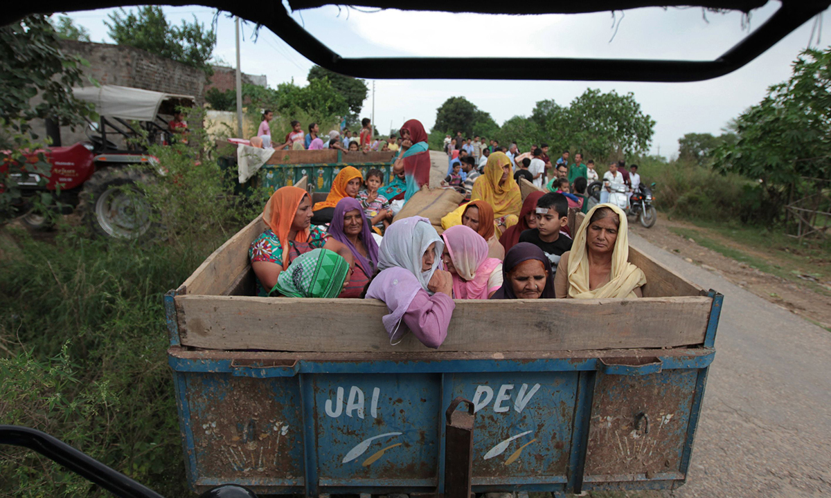 Indian villagers sit in a trailer as they prepare to leave the area following an alleged cross-border exchange between Indian and Pakistani soldiers at Chilayari village in Samba district, some 50 kms from Jammu on October 8, 2014. — Photo by AFP