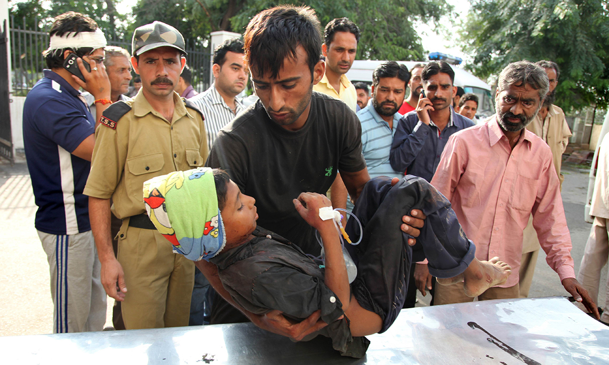 Indian residents bring a child reportedly injured in a cross-border exchange between Pakistani and Indian troops to a medical facility in Jammu on October 8, 2014. — Photo by AFP