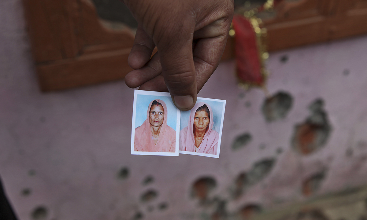 A neighbor displays photographs of Poli Devi, left and Shakuntla Devi, two women allegedly killed in firing from the Pakistan side of the border at Chilyari village of Samba sector in Jammu and Kashmir on October 8, 2014. — Photo by AP