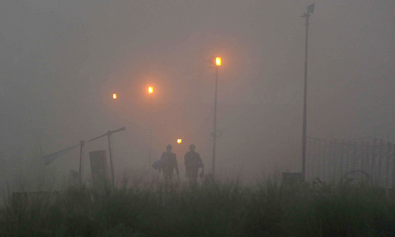 Photo shows Indian Border Security Force (BSF) soldiers walking through heavy fog at the India-Pakistan border, about 25 kms from Jammu on October 10, 2014.—AFP photo