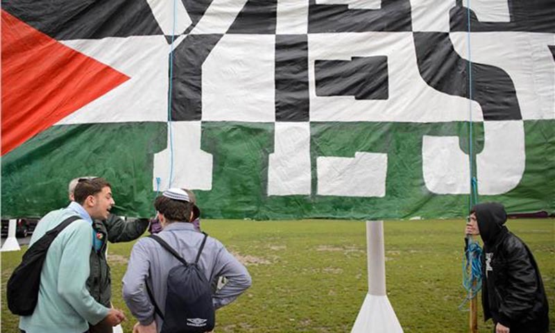 Young Jewish men argue with Pro-Palestinian supporters beside a giant banner calling for a recognised Palestinian State.— Photo by Reuters