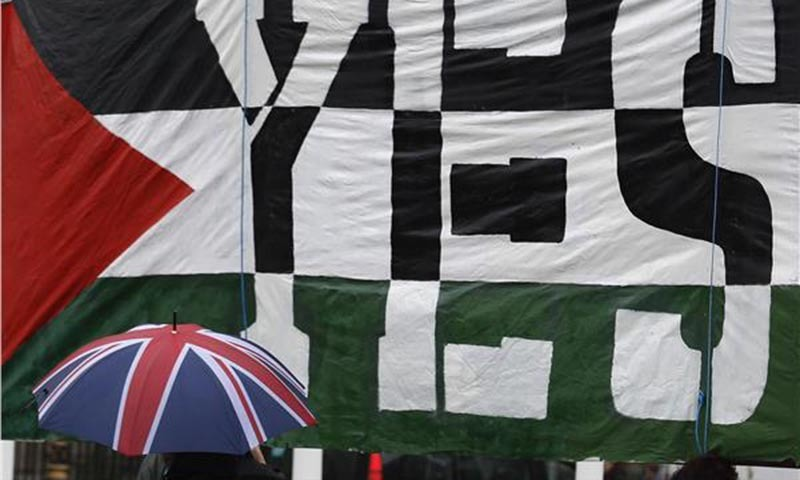 A passer-by carries a Union Flag umbrella past a pro-Palestine demonstration outside the Houses of Parliament in London October 13, 2014.—Photo by Reuters