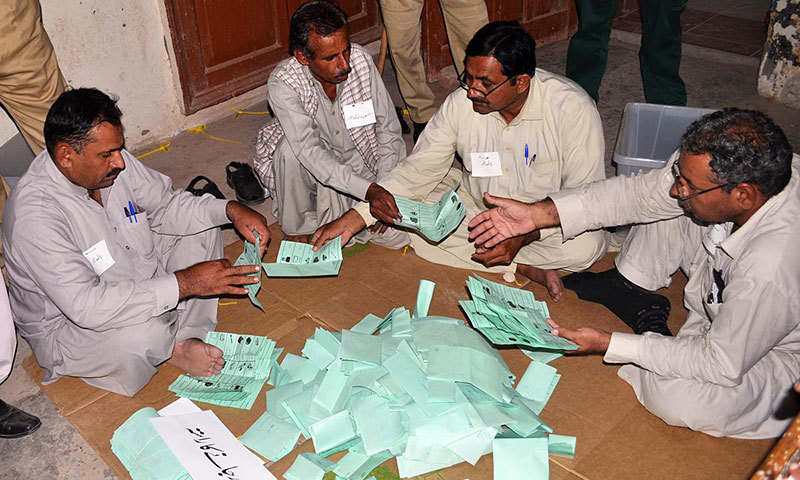 Polling staff count votes at a polling station after by-elections at NA-149 in Multan on Thursday. – Photo by Online