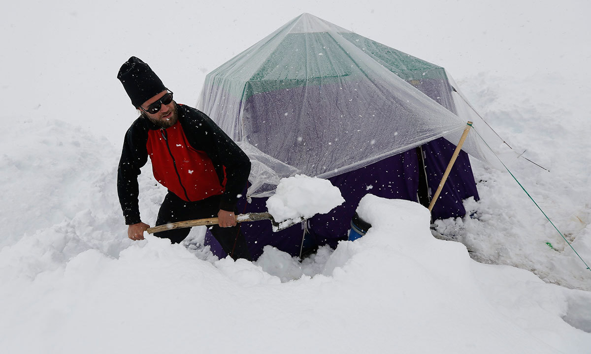 A German trekker removes snow from a kitchen tent at Concordia, the confluence of the Baltoro and Godwin-Austen glaciers, near the world's second highest mountain K2 (8,611 meters) in the Karakoram mountain range in Pakistan. -Reuters Photo
