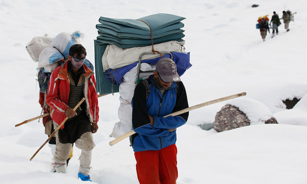 Porters make their way through deep snow on the Baltoro glacier in the Karakoram mountain range in northern Pakistan. -Reuters Photo