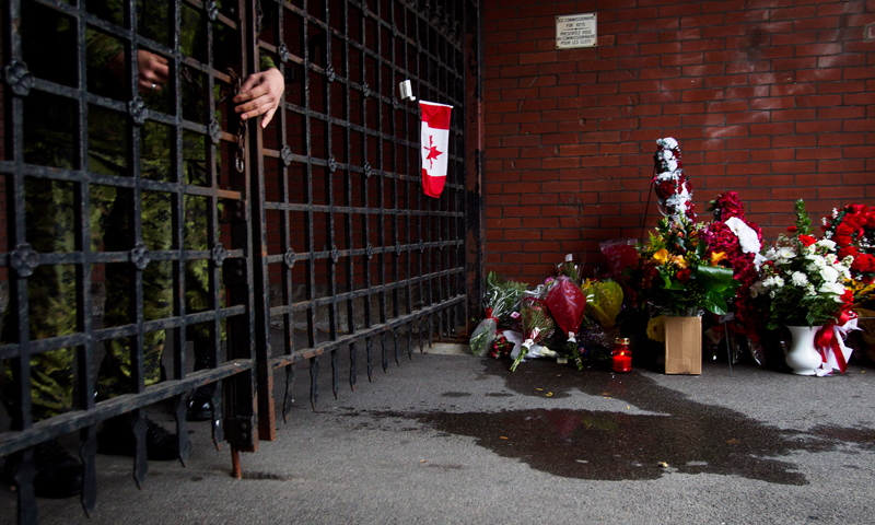 A soldier locks the gates as flowers are placed at a memorial outside the gates of the John Weir Foote Armory, the home of the Argyll and Sutherland Highlanders of Canada in Hamilton, Ontario, Wednesday, Oct 22, 2014, in memory of Canadian soldier Nathan Cirillo. — Photo by AP