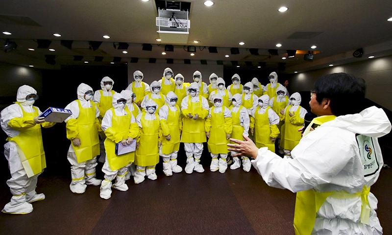 جنوبی کوریا کے ایک ہسپتال میں ڈاکٹروں اور نرسوں کو ایبولا سے محفوظ رکھنے والے لباس کو پہن کر کام کرنے کی تربیت دی جارہی ہے۔ —. فوٹو اے پی