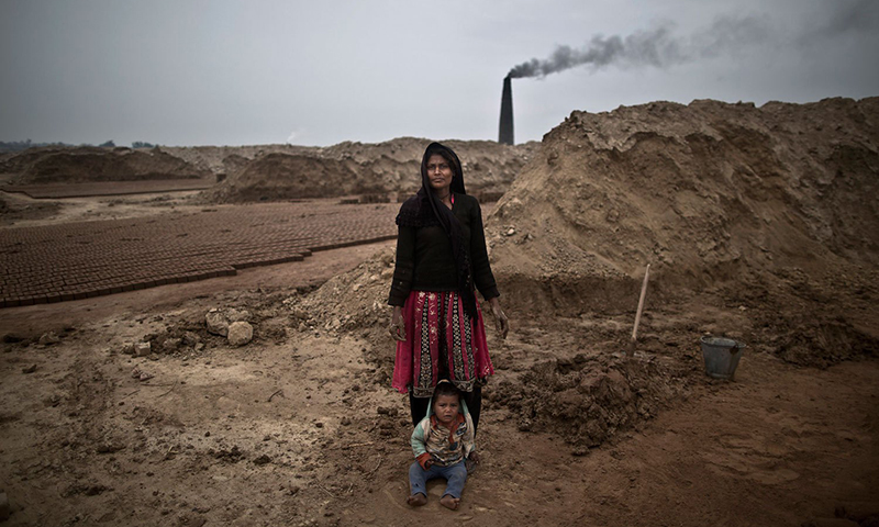 This picture shows a woman posing with her child at site of a brick factory in Mandra, near Rawalpindi. — File photo/AP