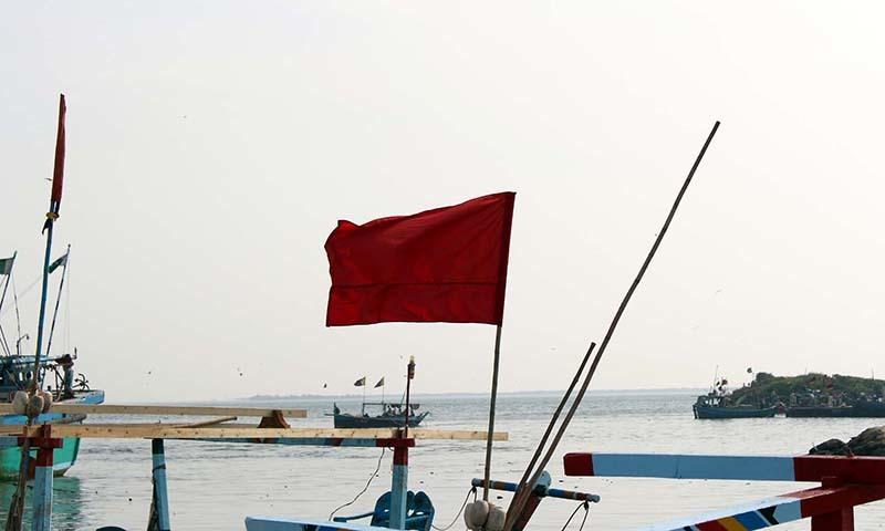 ایک ماہی گیر کشتی میں سرخ جھنڈا لہرا کر دیگر کو خراب سمندری صورتحال سے خبردار کیا جارہا ہے— فوٹو پی پی آئی