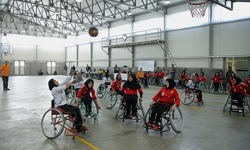 In this photo taken Tuesday, Oct. 28, 2014, a player from Balkh province (in withe) shoots the ball during a match against the team from Herat province (in red) in Afghanistan's national wheelchair basketball tournament organized by the International Committee of the Red Cross (ICRC) in Kabul, Afghanistan. — Photo by AP