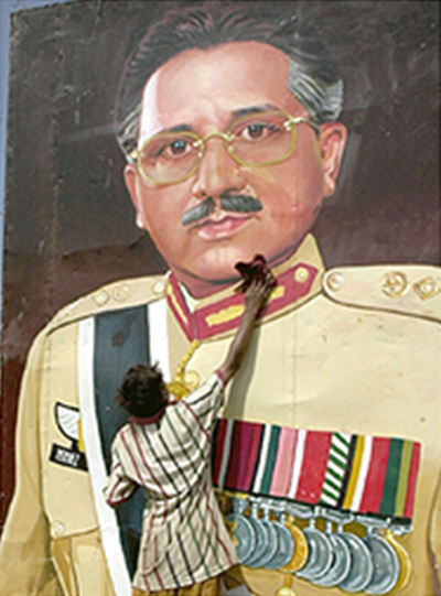 A man pasting a large poster of Musharraf in Lahore in 2002.