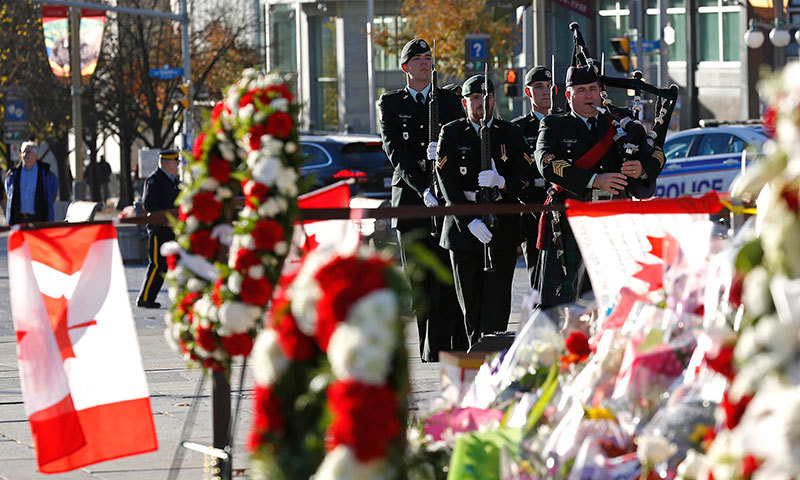 The day's first posting of the sentries, framed by flowers and wreaths left in tribute to Cpl. Nathan Cirillo, arrive at the National War Memorial in Ottawa October 30, 2014. Cirillo was killed during a shooting incident at the National War Memorial in Ottawa on October 22. – Reuters