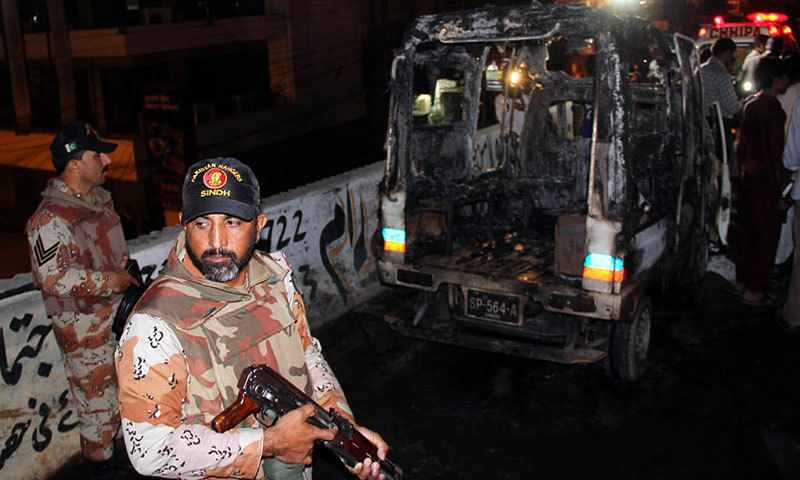 Security personnel stand guard near the burnt police mobile at Nipa flyover in Karachi on Friday. – Photo by Online