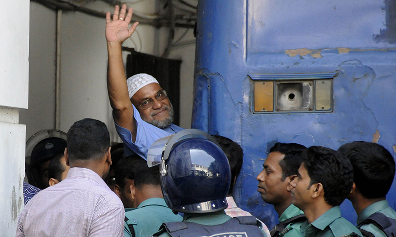 Bangladeshi Jamaat-i-Islami party leader, Mir Quasem Ali waves his hand as he enters a van at the International Crimes Tribunal court in Dhaka. — AFP