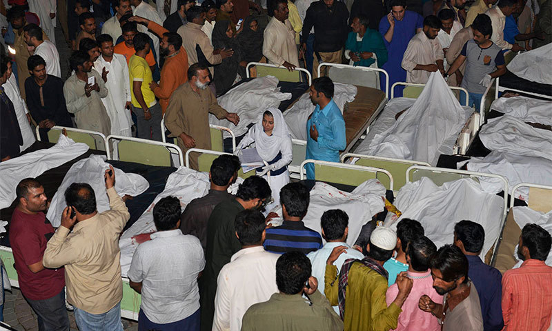 Relatives gather around the bodies of blast victims after a suicide bomb attack near the Wagah border. -AFP Photo