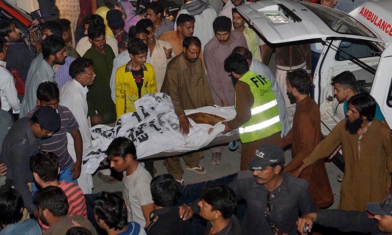 Volunteers transport the body of a blast victim after a suicide bomb attack near Wagah border on November 2, 2014. A suicide bomber killed at least 45 people November 2 at the main Pakistan-India border crossing - AFP