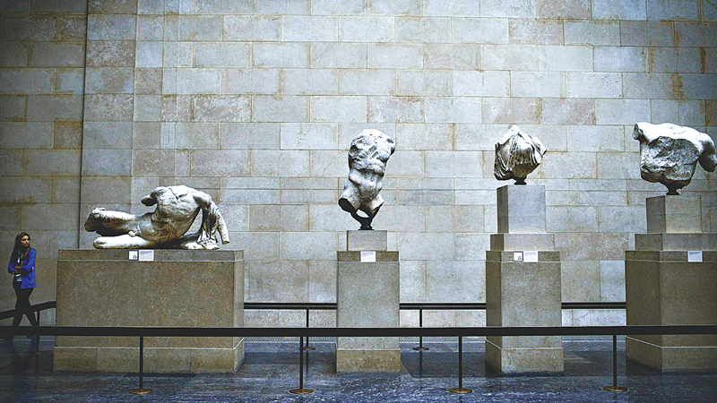 A woman looks at the Parthenon marbles, a collection of classical Greek marble sculptures, also known as the Elgin marbles, on show at the British Museum in London.