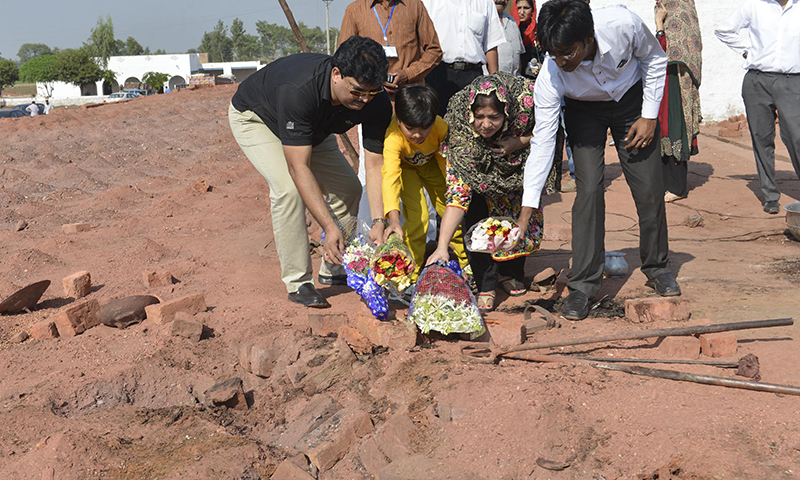 Relatives lay flowers at the site of the murder of the Christian couple at a brick kiln in Kot Radha Kishan, some 60 kilometres (40 miles) southwest of Lahore on November 5 - AFP