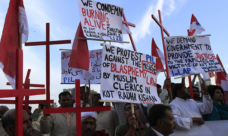 Members of the Christian community hold placards and wooden crosses during a demonstration to condemn the death of the Christian couple - AFP